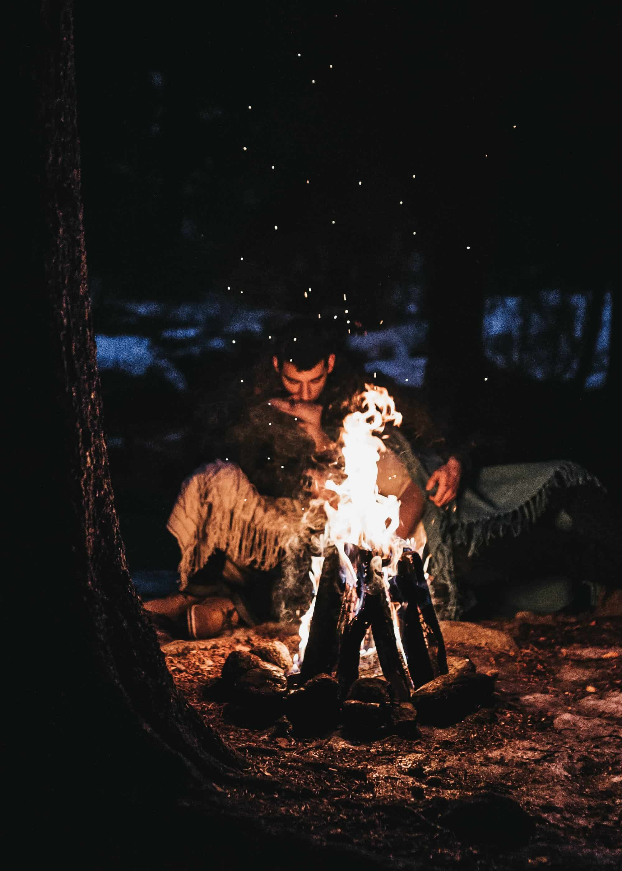 couple kissing around a bonfire at night in Colorado mountains