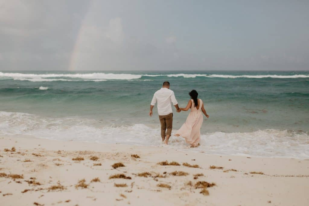 couple in the beach in Cancun Mexico with a rainbow behind them