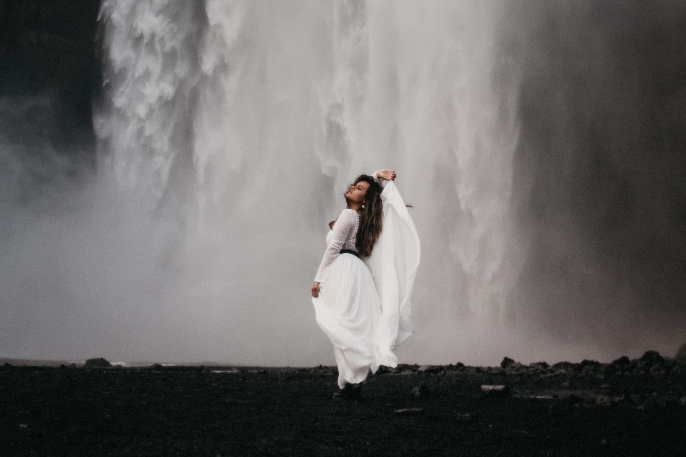 Bride posing in from of Skogafoss waterfall in Iceland