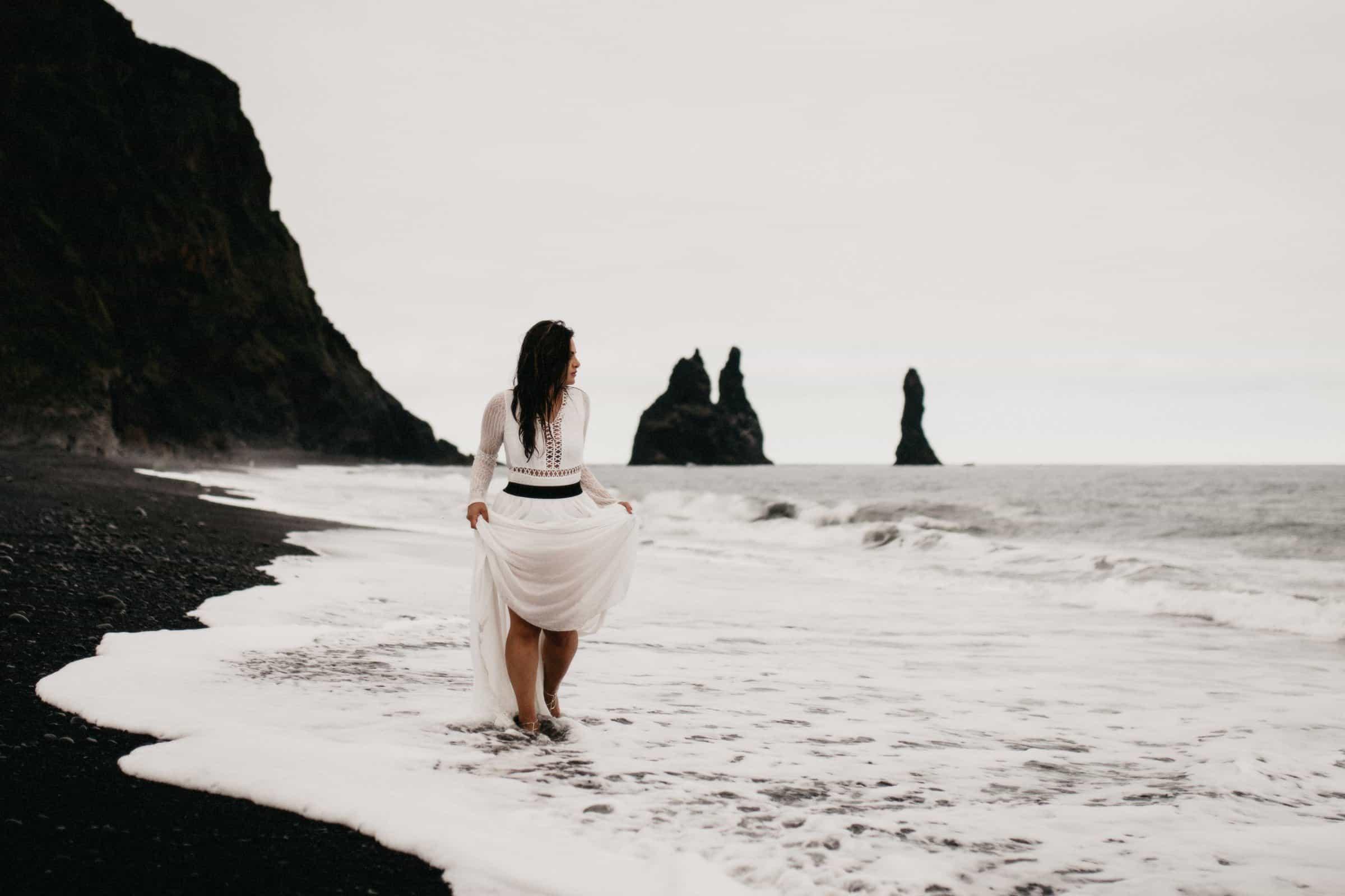 bride walking barefoot as waves hit her feet at Reynisfjara black sand beach in Iceland