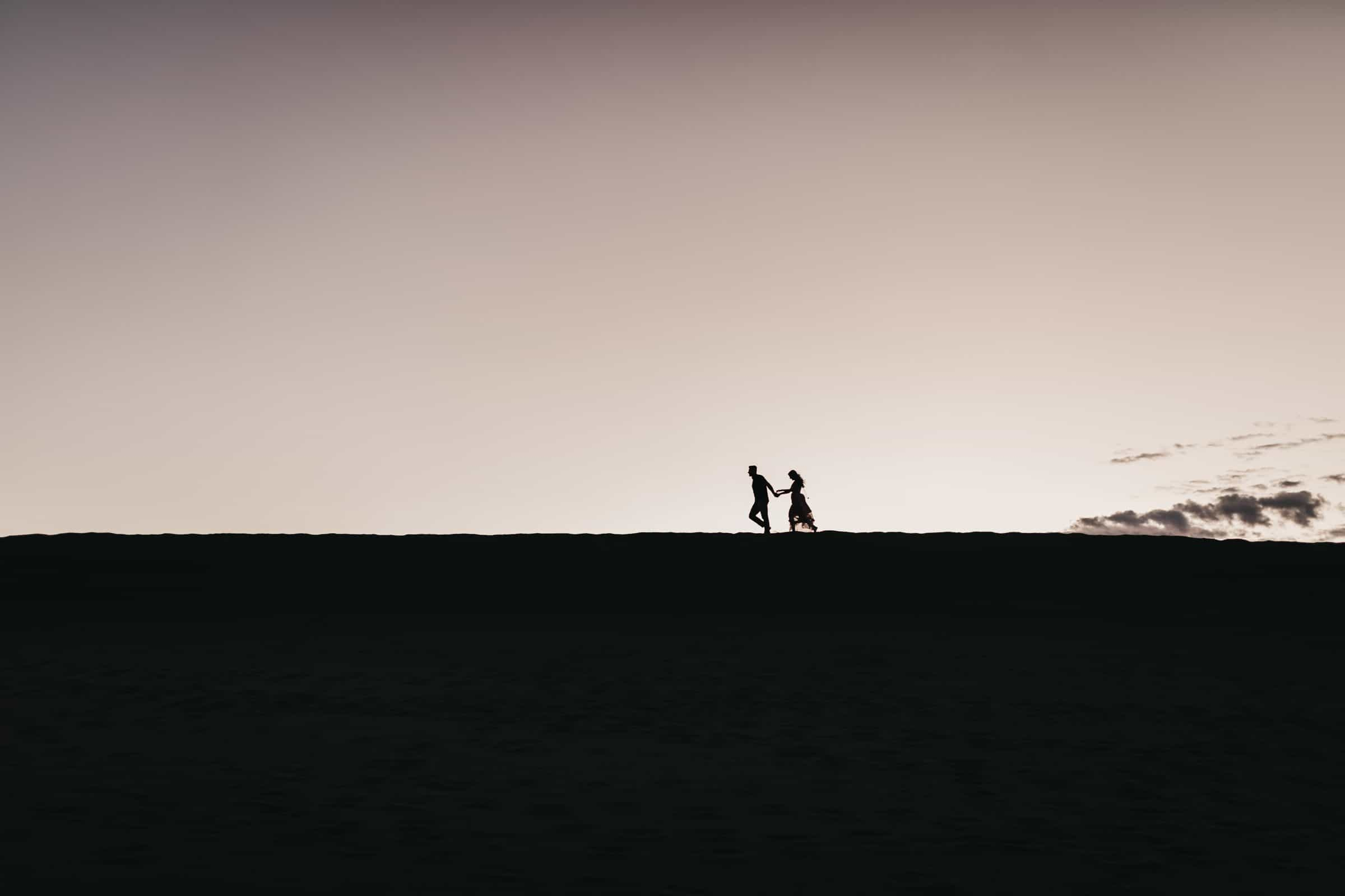 silhouette of couple running over the horizon of sand dunes during sunrise