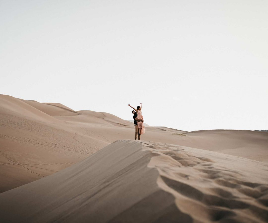 Couple in the Colorado sand dunes during sunrise