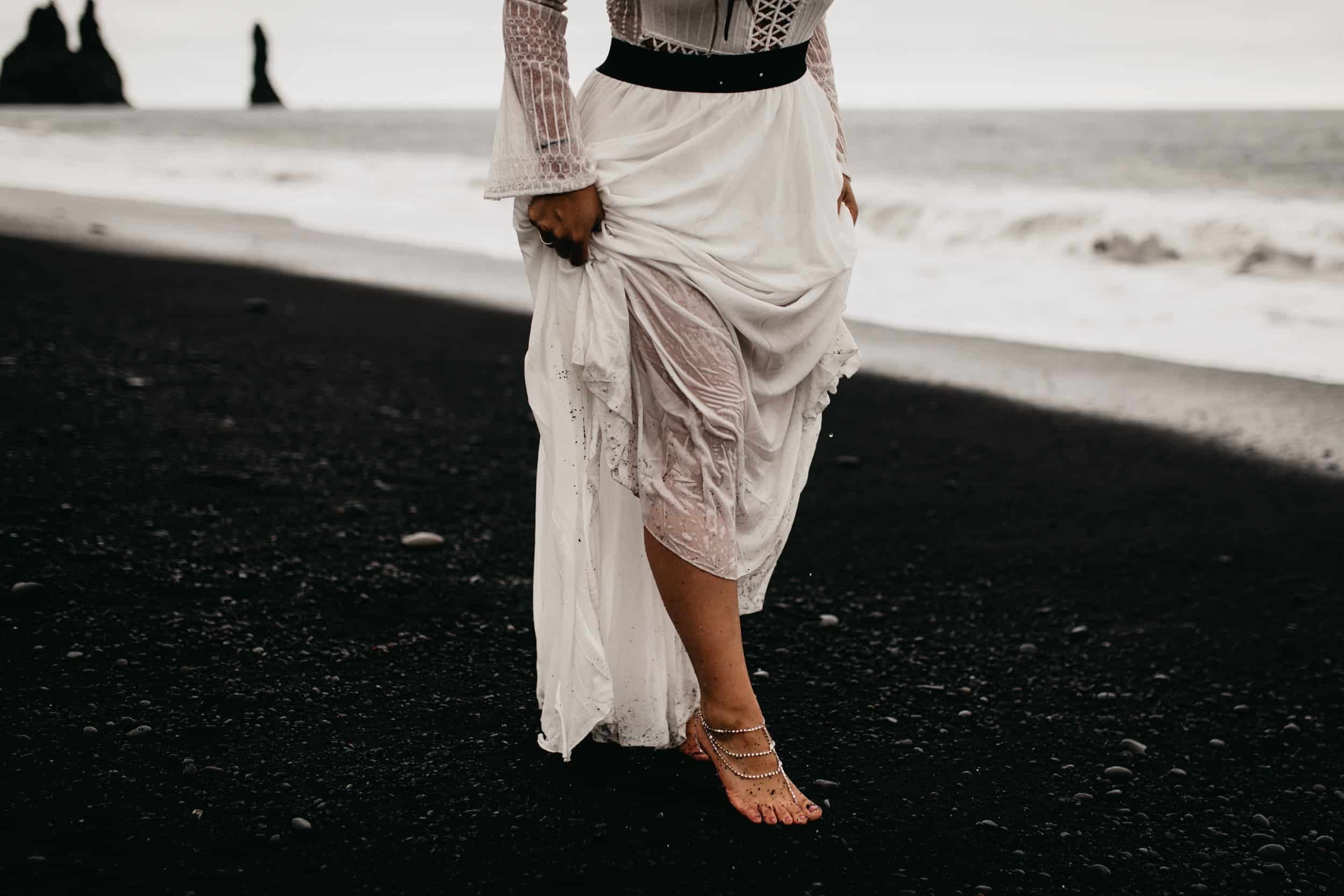 bride walking barefoot on a black sand beach in Iceland