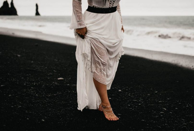 close up of bride walking barefoot on the black sand of Reynisfjara beach in Iceland as she holds up her wet dress