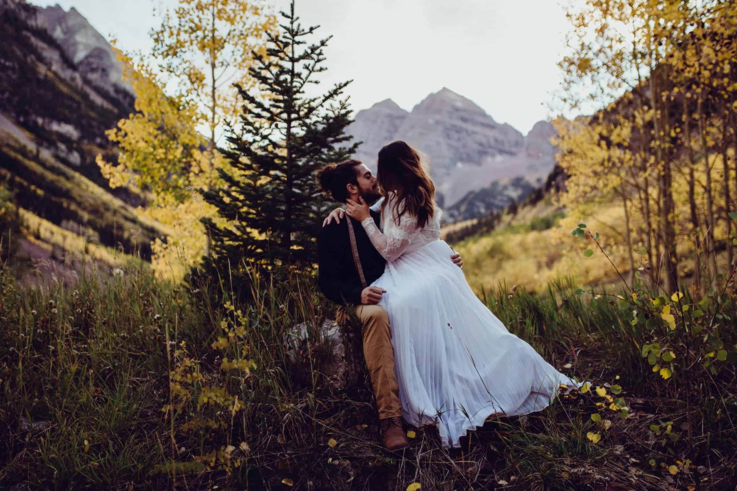 bride sitting on husbands lap as she kisses him. They sit in a rock with a beautiful Mountain View behind them