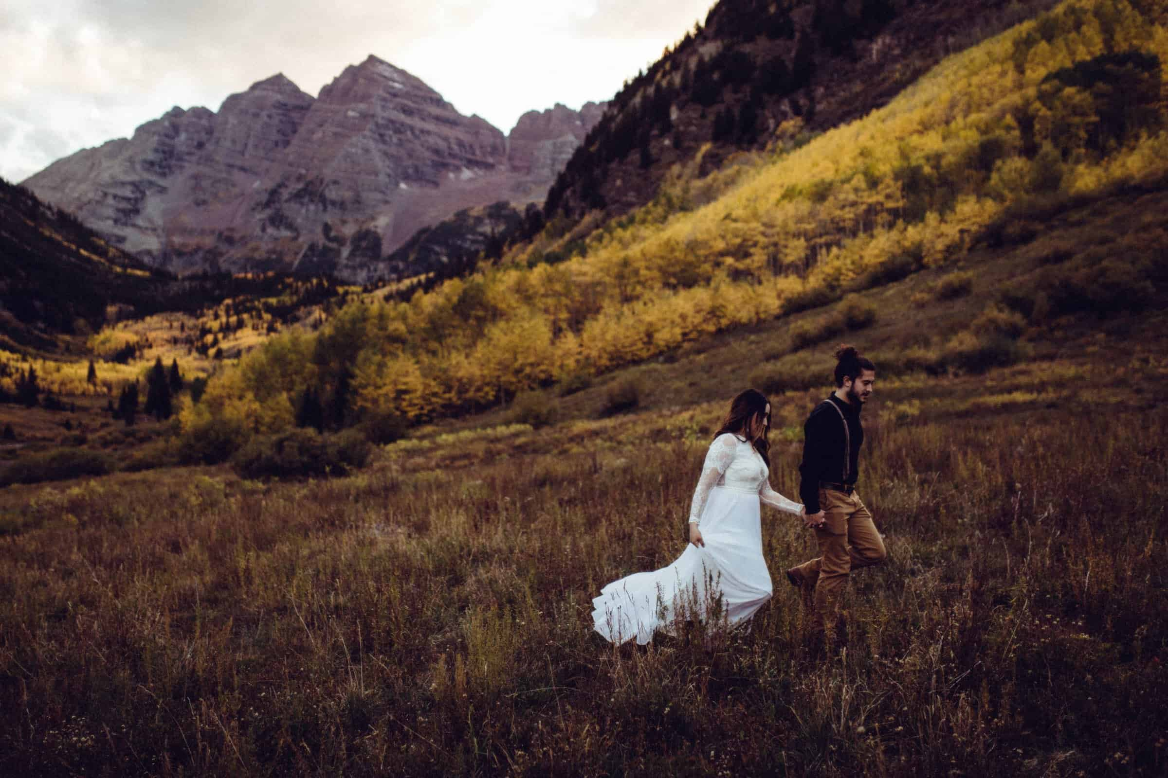 bride and groom walking hand in hand through an open field in the mountains surrounded by fall foliage