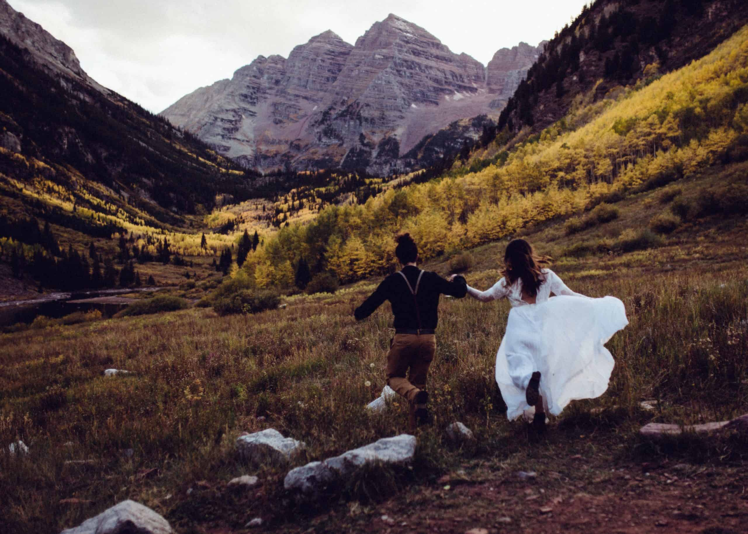 bride and groom running hand in hand in aspen Colorado mountains