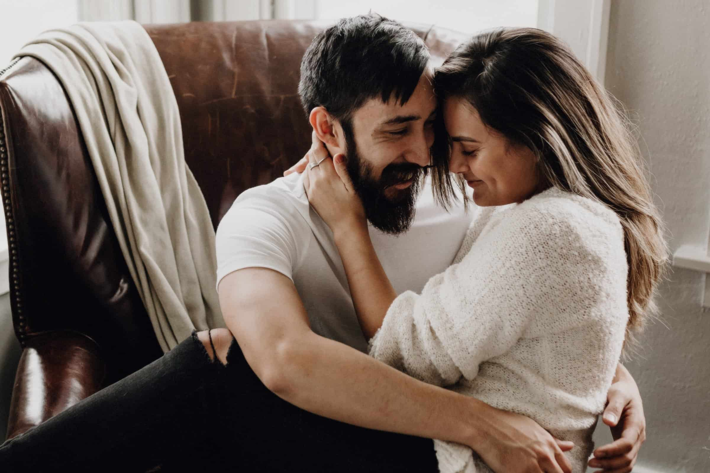 couple hugging and laughing together as the girl sits in the guy's lap.