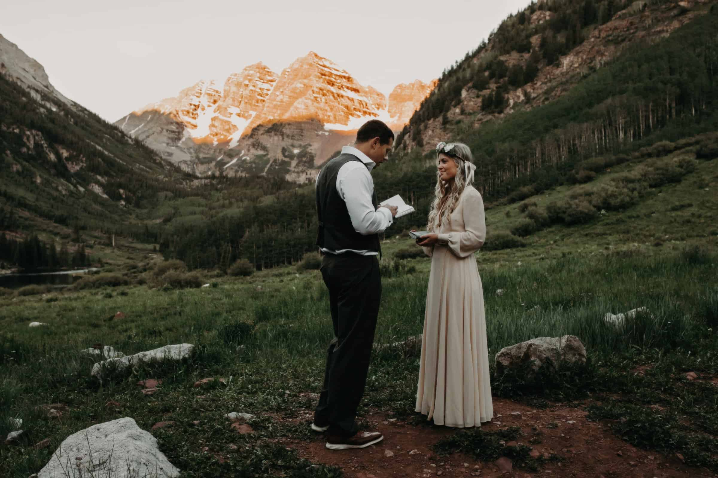 couple exchanging vows during their vow renewal at the Colorado Maroon Bells during sunrise